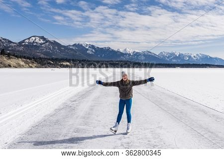 Invermere, Canada - March 17, 2020: Girl On Frozen Windermere Lake And Rocky Mountains In British Co
