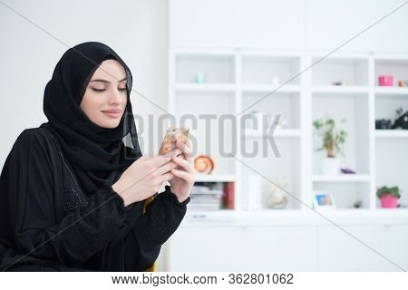 young modern muslim business woman using smartphone wearing traditional hijab clothes at home