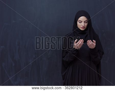 portrait of beautiful muslim woman in fashionable dress with hijab making traditional prayer to God, keeps hands in praying gesture isolated on black chalkboard background representing modern islam