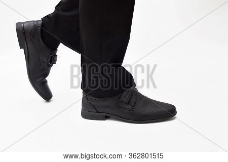 Male Legs In Black Classic Shoes And Black Trousers, School Shoes, Male Legs Step On A White Backgro