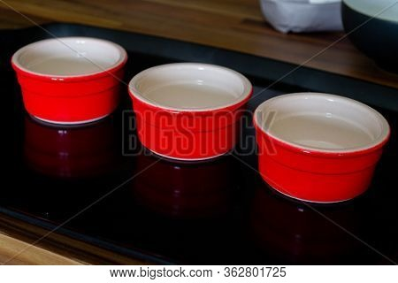 Three Red Ramekins Sitting On A Black Tray. The Black Tray Is On Top Of A Wooden Counter Top With Ge