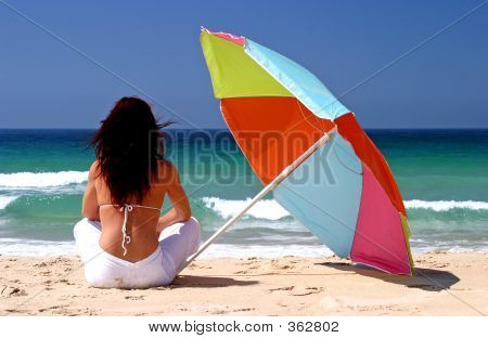 Woman Sitting Under Colorful Parasol On White Sandy Beach