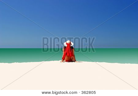 Woman In Red Hat And Bikini Sitting All Alone On Empty Beach