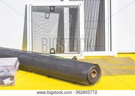 Bright Sun. Yellow Background. A Roll Of Mosquito Net In The Foreground. In The Background Are Sever