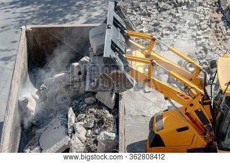 Bulldozer Loader Uploading Concrete Debris Into Dump Truck At Construction Site