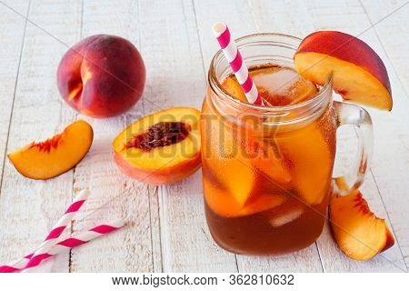 Homemade Peach Iced Tea In A Mason Jar Glass. Table Scene With A White Wood Background.