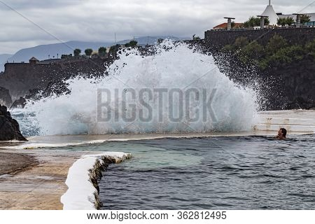 Porto Moniz Madeira - August 2, 2018: A Girl Bathes In A Natural Lava Pool During High Tides And Lar