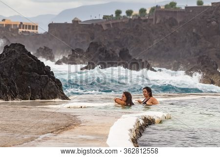 Porto Moniz Madeira - August 2, 2018: Girls Bathes In A Natural Lava Pool During High Tides And Larg