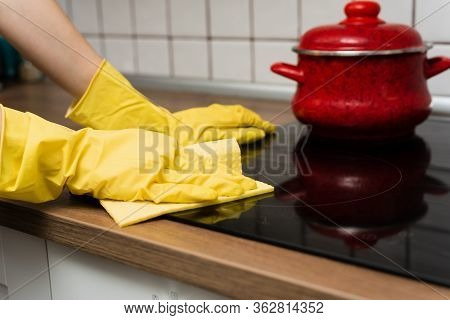 Someone Is Washing A Kitchen Stove In Yellow Gloves. Someone Is Cleaning A Kitchen With Rag.