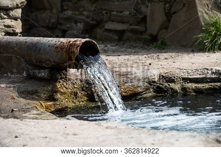 Stream Of Water From A Rusty Metal Pipe Flows Into A River