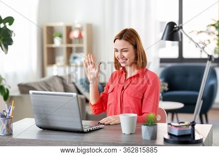 remote job, technology and people concept - happy smiling young woman with laptop computer having video call and waving hand at home office