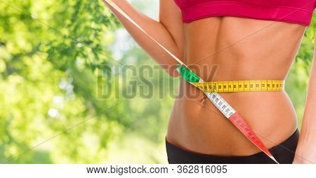 weight loss, slimming and diet concept - close up of woman measuring her waist with tape measure over green natural background