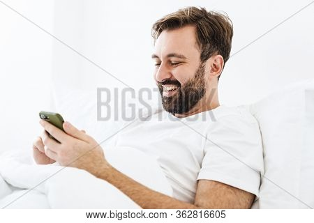 Image of young unshaven caucasian man smiling and using cellphone while lying in bed at home