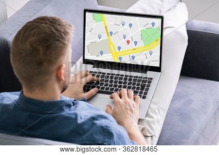 Close-up Of A Man Using Gps Map With Navigation Pointers On Laptop