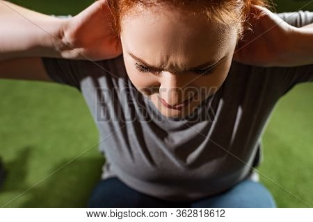 Overhead View Of Purposeful Overweight Girl Doing Abs Exercise On Fitness Machine