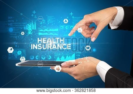 Close-up of a touchscreen with HEALTH INSURANCE inscription, medical concept