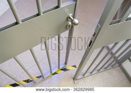 Metal Bars In Prison. Opened Jail Cell Door. The Lock And Steel Bobble Handle Closeup . Safety Line.