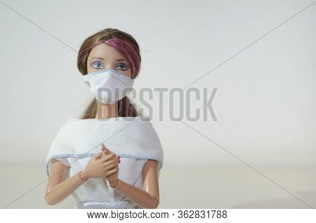 Barbie Doll Portrait With Face Mask And Joined Hands On White Background.