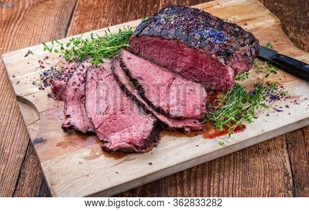 Traditional Commonwealth Sunday roast with sliced cold cuts roast beef with herbs and salt as closeup on a rustic wooden cutting board