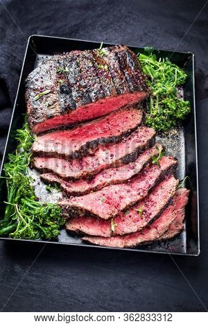 Traditional Commonwealth Sunday roast with sliced cold cuts roast beef with vegetable broccoli and salt as closeup on a rustic metal tray