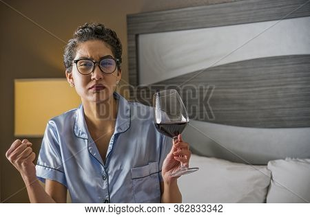 An Angry Woman Wearing Satin Pajamas Sits In Bed With A Glass Of Wine