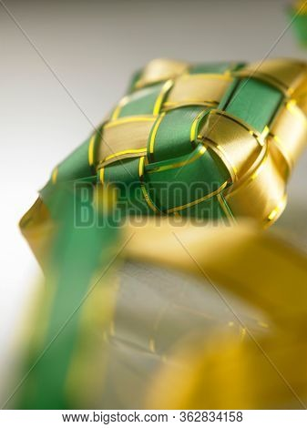 selective focus on ribbon ketupat on the marble table with reflection