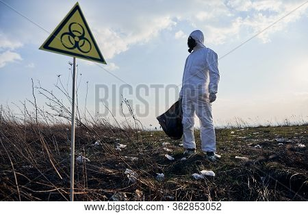 Environmentalist In Protective Suit And Gas Mask Holding Garbage Bag, Standing Near Biohazard Sign O