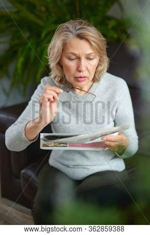News, Press, Media, Holidays And People Concept - Woman Reading Newspaper At Home
