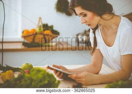 Young Woman Looking For A New Recipe For Cooking In A Kitchen. Housewife Is Making Online Shopping B