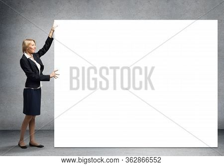 Beautiful Woman In Suit Standing Near Big White Banner. Blank Whiteboard Template With Copy Space Fo