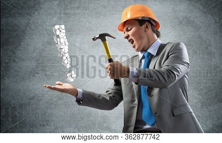 Furious Businessman Going To Crash With Hammer Exclamation Mark. Young Handsome Man In Business Suit