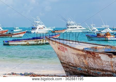 Punta Cana, Dominican Republic - March 11, 2020: Old Boats And Modern Yachts On A Beach In Punta Can