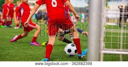 Young Boy Soccer Player Scoring Goal In Match. Junior Level School Footballers Kicking Soccer Tourna