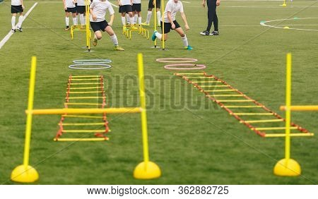Soccer Field With Training Equipment And Players With Coach In Background. Junior Football Team Trai