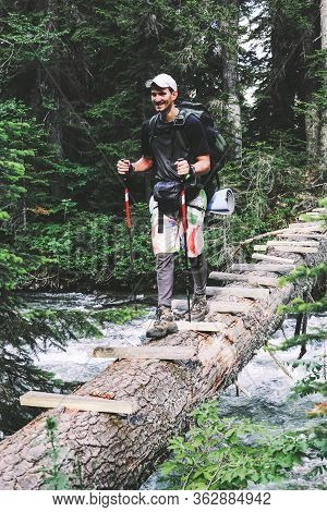 Man Traveler With Backpack Hiking The Bridge Over A River The Expedition, Travel Lifestyle Concept.