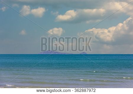 Beach With Clear Water With Clear Blue Calm Sea And Mountains On The Background And Beautiful Sky.su