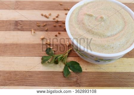 Bowl Full Of Sprouted Fenugreek Hair Mask With Scattered Fenugreek Seeds And Leaf