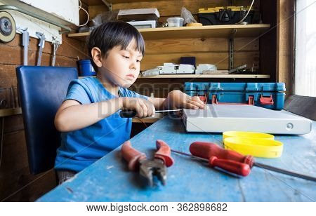 A Small Child Works In A Workshop