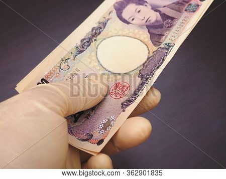 A Hand In A Flesh-colored Latex Glove Holds A Bundle Of Japanese Money. Above Is A 5000 Yen Bill. Da