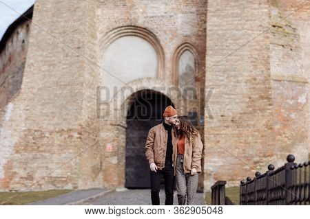 Young Happy Couple On Old City Background. A Love Couple Enjoying A Walk In The Courtyard Of The Old
