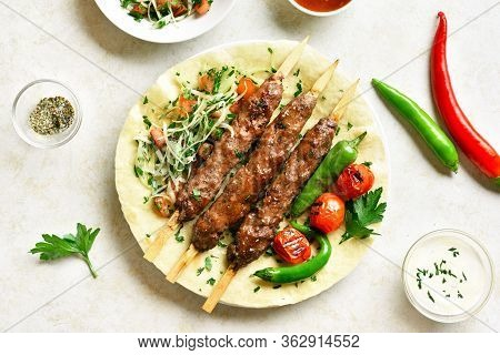Turkish Adana Kebab With Fresh Vegetables On Flatbread Over Light Stone Background. Top View, Flat L
