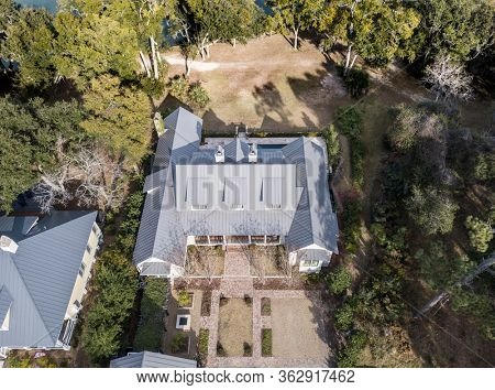 High angle aerial view of expensive house with metal roof on landscaped property.