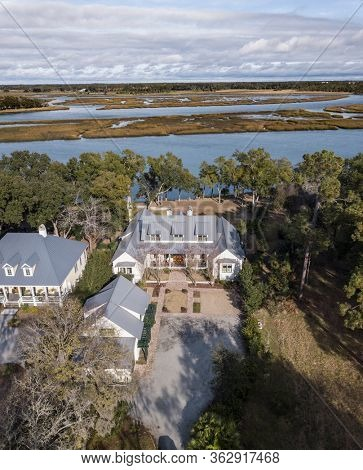 Aerial view of expensive house with metal roof with waterfront view.