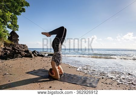 Young Woman In Black Doing Her Yoga On Asian Sand Beach Sirshasana (headstand Upside-down) Pose. Hea