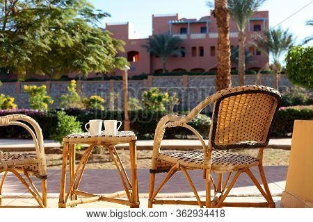 Table And Rattan Wicker Seat Chair. Wicker Furniture Rattan Table Two Chairs Near The Window On Balc