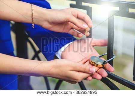 The Bride And Groom Hang The Wedding Lock On The Bridge. The Keys And The Padlock Symbol Of Love And