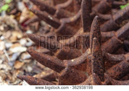 Old Agricultural Machinery In Disuse And Rusted. Detail In The Foreground