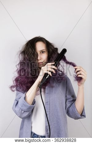 Young Girl Straightens Curly Hair Of Flat Iron. Coloring Purple Hair. Gray Background