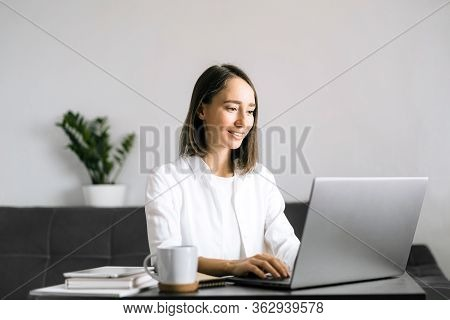 Happy Young Woman Sitting At The Table And Using Laptop, Calling By Video Chat.