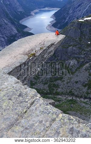 Sitting On The Edge Of Troll's Tongue In Norway. Tourist Attraction Known As Trolltunga. Rock Pulpit